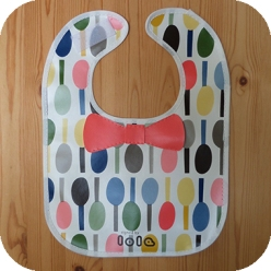 Cute Lola oilcloth baby bib with bow tie